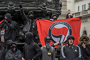 Anti Fascist gather in Piccadilly Circus in black with masks to hide themselves from Police surveillance - A march against racism, organised by Stand Up to Racism and supporterd by the TUC and most major unions including Unison, Unite, The PCS and the NUT. It started in Portland place and ended up in Parlaiment Square, Westminster - London 18 Mar 2017.