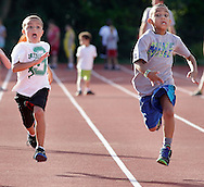 Alex Price, left, and  Elijah Beamon race to the finish line on the Middletown High School track during the Twilight Track and Field Series on Tuesday, July 30, 2013.