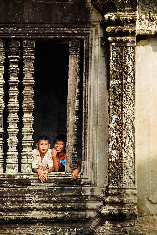 Two local boys amongst the carved ruins of Angkor Wat temple, Cambodia.