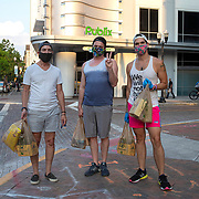 The grocery shoppers are seen on the sidewalk wearing protective masks due to the Coronavirus (Covid-19) pandemic at Lake Eola Park Publix on Tuesday, April 15, 2020 in Orlando, Florida. (Alex Menendez via AP)