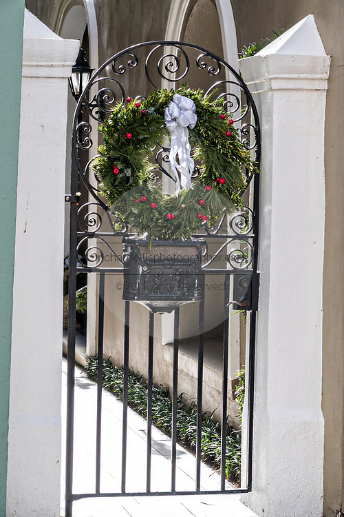 A traditional evergreen Christmas wreath decorates the garden gate on a historic home in Charleston, SC.