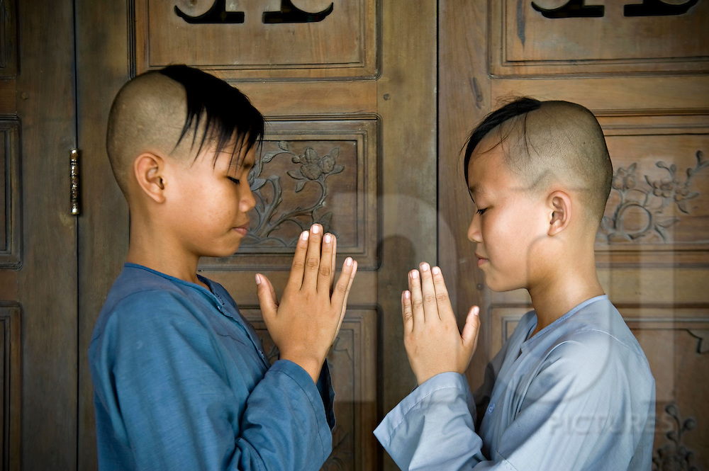 Young vietnamese buddhist monks praise with folded hands posture. They face each other. Vietnam, Asia