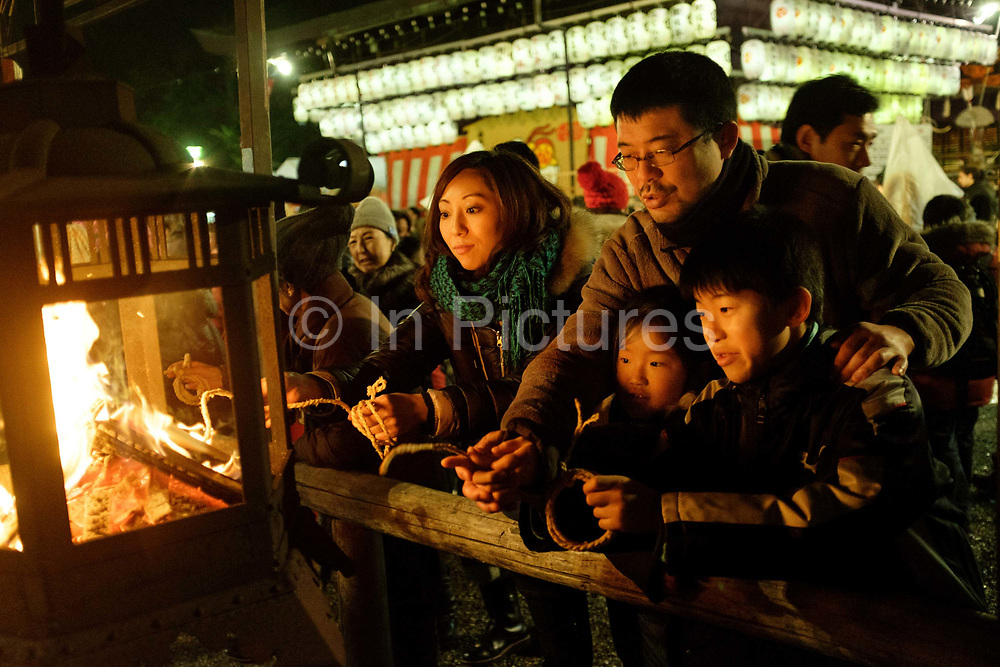 New Year's Eve celebrations at the Yasaka Shrine. The traditional ritual consists of burning thin slats of wood onto which people have written their wishes. Shine goers also light a straw rope from the fire which they twirl and take home with them.