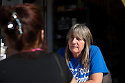 Executive Director Karen Kolander, of Milpitas, talks with beneficiaries at the Milpitas Food Pantry in Milpitas, California, on November 25, 2014. (Stan Olszewski/SOSKIphoto)