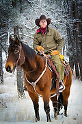 Cowboy (Tommy) on his horse in a wooded area near New Haven ranch in Wyoming