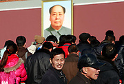 "Visitors walk under a portrait of Mao Zedong (Mao Tse-tung) at the Tiananmen Square in Beijing, China, on 10 December 2011.  Tiananmen Square is considered the symbolic center of all China, it's significance is not lost on China's current leaders as it tightens its security and surveillance of the area to spot potential ""trouble makers"""