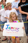 A young turtle fan holds a sign for one of the rehabilitated Loggerhead Sea Turtles released by the South Carolina Aquarium May 18, 2012 in Isle of Palms, South Carolina.