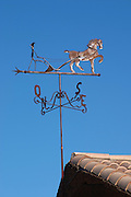 Weather vane with compass directions, depicting a horse and a man that is ploughing a field with a plough. Domaine Fontedicto, Caux. Pezenas region. Languedoc. France. Europe.