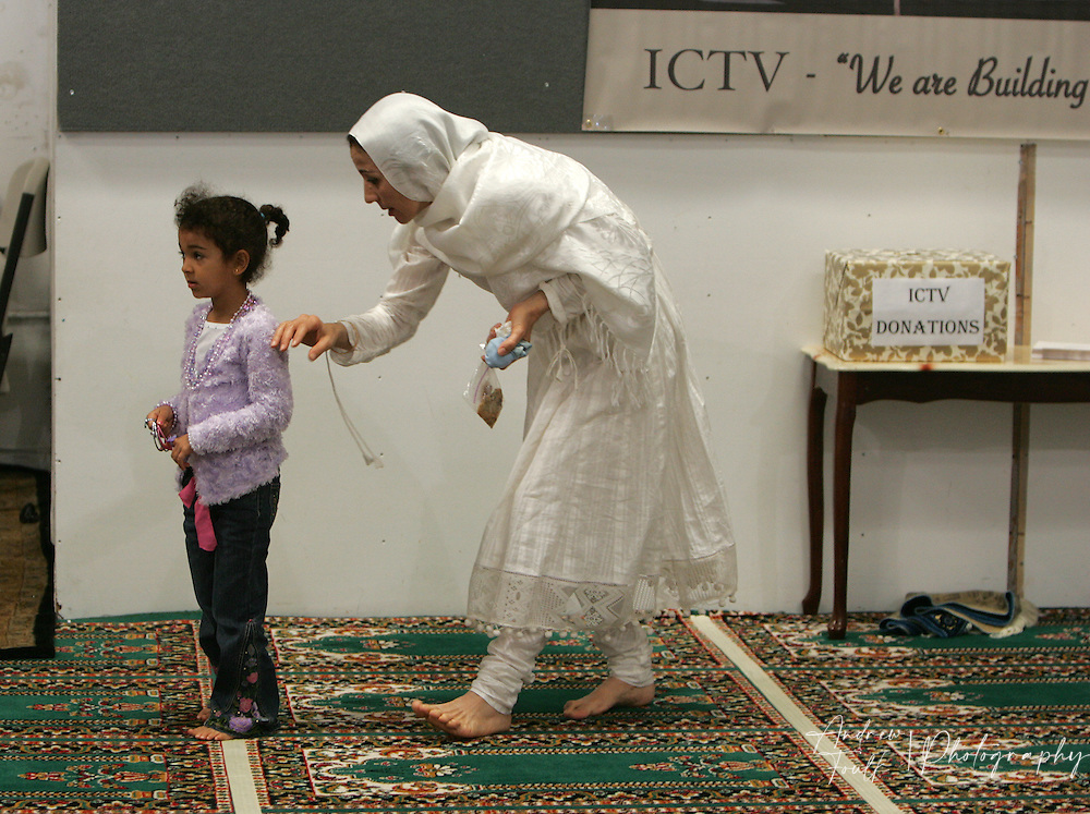 /Andrew Foulk/For The Californian/.A female worshiper at the Islamic Center of Temecula puts her hand on the shoulder of a young girl after the end of services for the final day of Ramadan.