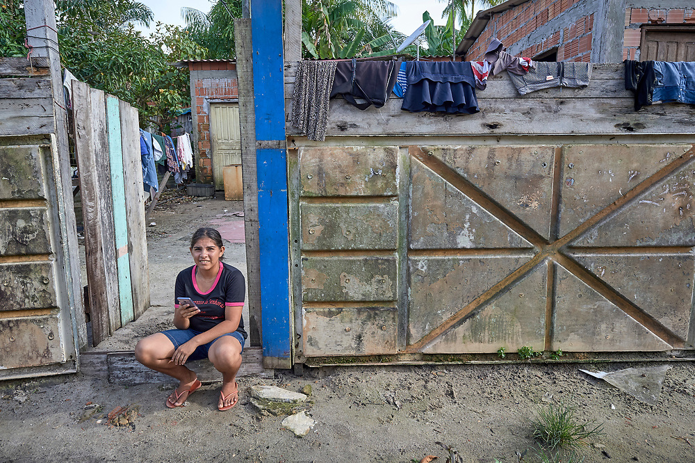 An indigenous woman sits in the entry to her house in the Nacoes Indigenas neighborhood in Manaus, Brazil. The neighborhood is home to members of more than a dozen indigenous groups, many of whose members have migrated to the city in recent years from their homes in the Amazon forest.