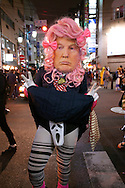 """October 29, 2016, Tokyo, Japan: A humorous Japanese crossdresser makes a political statement about Donald Trump while dressed in school girl's uniform with """"Scream"""" mask underneath his skirt. This was in the Shinjuku Ni-chome gay district of Tokyo where Halloween celebrations were in full swing, both risque and flamboyant. Halloween celebrations have exploded in the past few years in Japan and up until recently were minimal across the city and Japan. When Oct. 31 falls on a weekday, ninety percent of Halloween celebrations across Japan take place on the preceding Saturday. (Torin Boyd/Polaris)."""