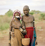 Mursi tribal man and woman with plate in lip, Omo Valley, Southern Ethiopia. The Mursi consider the lip plate as a form of beauty.