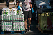 A volunteer distributes corn masa flour to local residents during a pop up grocery event at Powderhorn Park in Minneapolis, Minnesota, U.S., on Friday, July 24, 2020. Photographer: Ben Brewer/Bloomberg