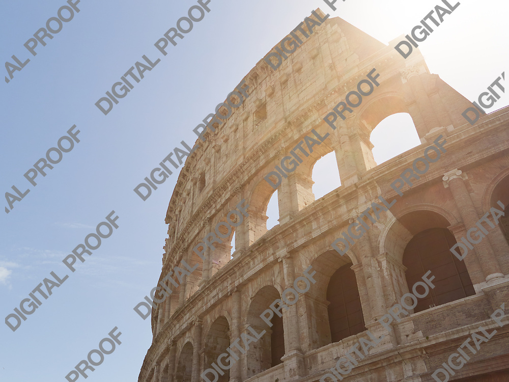 View of Colosseum with flare in a sunny day with little clouds