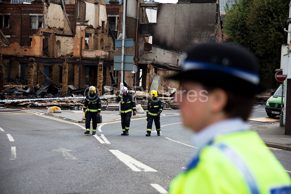 Firefighters pass the burnt out remains of two furniture businesses at Reeve Corner in Croydon. The day after rioting took place in Croydon in South London. Riots flared for a third night in a row, resulting in burnt out buildings, looted shops and general smashed up devastation.