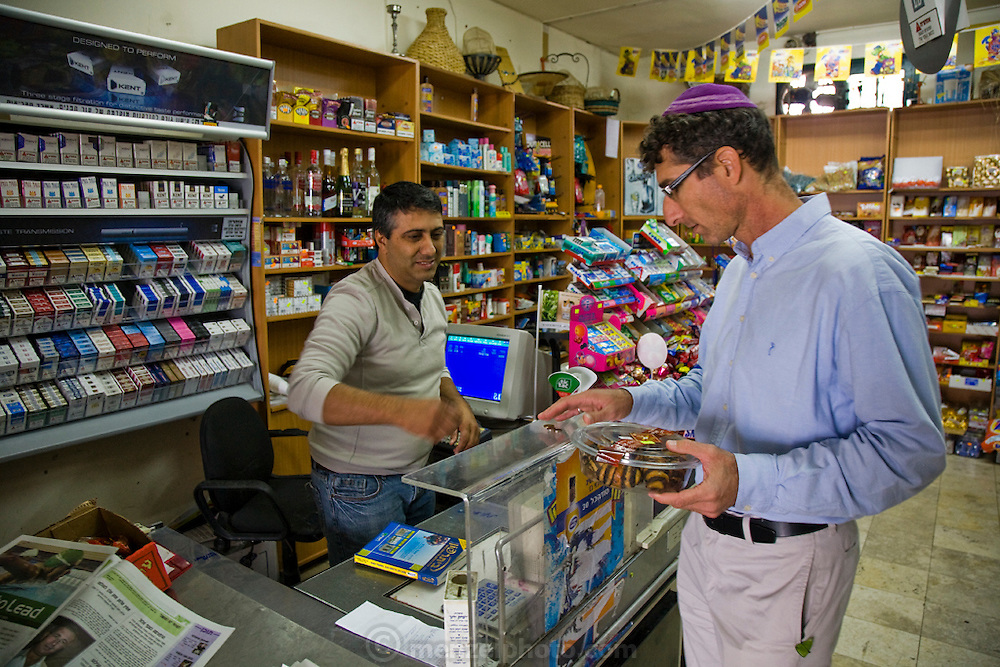 Ofer Sabath Beit-Halachmi, a Reform rabbi, pays for rugelach pastries at a grocery store near his home in Tzur Hadassah, Israel.  (Ofer Sabath Beit-Halachmi is featured in the book What I Eat: Around the World in 80 Diets.) The caloric value of his typical day's worth of food in the month of October was 3100 Kcals. He is 43 years of age; 6 feet, 1 inch tall and 165 pounds. Ofer's town in the Judean Hills about 15 minutes southwest of Jerusalem is a communal settlement where residents lease land and houses from the state of Israel for a 99-year period. MODEL RELEASED.