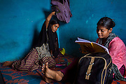 Poonam, 13, (right) is reviewing her homework as her older sister Jyoti, 14, is reaching her schoolbag for a pen, while sitting on the floor of their newly built home in Oriya Basti, one of the water-contaminated colonies in Bhopal, central India, near the abandoned Union Carbide (now DOW Chemical) industrial complex, site of the infamous '1984 Gas Disaster'.