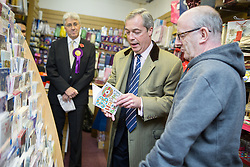 """© Licensed to London News Pictures . 03/11/2015 . Oldham , UK . UKIP leader NIGEL FARAGE (c) buying an 80th birthday card for his father from """" Greetings """" card and gift shop , from shop manager DAVID LOWICK (r) , in Royton Shopping Centre , at the launch of the party's campaign for the seat of Oldham West and Royton . The by-election has been triggered by the death of MP Michael Meacher . Photo credit : Joel Goodman/LNP"""