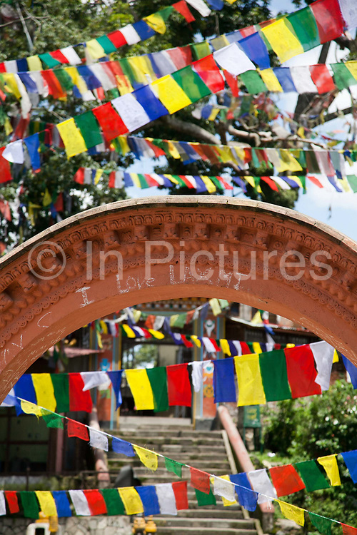 Buddhist prayer flags criss-crossing the sky at at the Swayambhunath temple complex, also called the Monkey Temple. The arc has been inscribed 'I love Laxmit'. The temple complex is a popular palce for young lovers to meet.