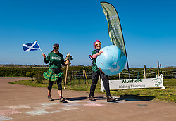 East Lothian, Scotland, United Kingdom, 25th April 2021. Virtual Kilt Walk: Kilt walkers supporting Muirfield Riding Therapy charity cross a 'finish line' to celebrate their participation in their 'Round the World'  fund raising campaign. Each team chose a destination and walked, cycled or rode the miles from home to their chosen point, totalling the 24,900 miles of the earth's circumference and raising over £10,000. Pictured: Shirley, Centre Manager, and Susan Law, staff at the charity. Sally Anderson / EdinburghElitemedia.co.uk