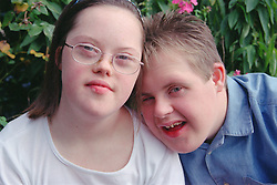 Portrait of teenage boy and girl with Downs Syndrome standing together in park,
