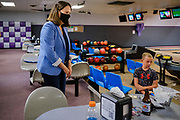 14 JULY 2020 - ADEL, IOWA: A child watches THERESA GREENFIELD walk through the Adel Family Fun Center, a bowling alley in Adel, IA, about 25 miles west of Des Moines. Theresa Greenfield, a Democrat, is running for the US Senate against incumbent Senator Joni Ernst. Recent polls have Greenfield slightly ahead of or statistically tied with Ernst, who is closely allied with President Donald Trump. This was one of Greenfield's first live campaign events since the Coronavirus pandemic shutdown started in March. She has been campaigning virtually using teleconferencing apps.     PHOTO BY JACK KURTZ