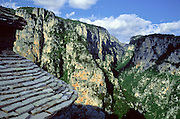 """See Vikos Gorge from the slate Agias Paraskevis Monastery, in Zagoria, north Pindus Mountains (Pindos or Pindhos), Epirus/Epiros, Greece, Europe. Vikos Gorge is the world's deepest canyon in proportion to its width, and at one point measures 2950 feet (900 meters) deep and 3600 feet (1100 meters) wide from rim to rim. Its depth is an impressive 82% of its width at that cross-section (depth/width ratio=0.82). Gorges in many countries have higher depth/width ratio, but none are as deep. The northeast wall of Vikos Gorge is Mount Tymfi (or Greek: , also transliterated Mt Timfi, Tymphe, or Tymphi), near the 40 degree parallel. Tymfi forms a massif with its highest peak, Gamila, at 2497 meters (8192 feet), the sixth highest in Greece. Zagori (Greek: ) is a region and a municipality in the Pindus mountains in Epirus, in northwestern Greece. Zagori contains 45 villages collectively known as Zagoria (Zagorochoria or Zagorohoria). Published in """"Pindos: The National Park"""" (2010) by Alexander G. Tziolas, preface by Tom Dempsey et al, ISBN 978-960-98795-3-8."""
