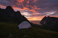 Colorful summer sunset over tents wild camping in mountains above Bunes beach, Moskenesøy, Lofoten Islands, Norway