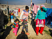 04 MARCH 2017 - KATHMANDU, NEPAL: Camp residents walk through an IDP camp in the center of Kathmandu. The camp opened days after the April 2015 earthquake devastated Nepal, killing almost 9,000 people. At its peak, about 1,800 families lived in the camp. The camp is still open nearly two years after the earthquake, about 400 families currently live in the camp. Camp residents say the Kathmandu municipal government is trying to close the camp and is encouraging residents to find new housing. They said the government is cutting off services to the camp and last week stopped the free distribution of water, although water can be purchased for delivery. Most of the people in the camp came to Kathmandu from rural villages in the mountains in the weeks after the earthquake. Many of the residents of the camp, technically homeless, have found work in Kathmandu's bustling construction industry, rebuilding homes destroyed in the earthquake.       PHOTO BY JACK KURTZ