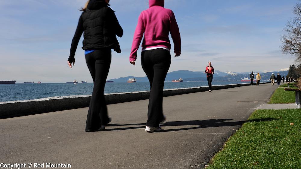 People walking and jogging along the path at English Bay, Vancouver, B.C