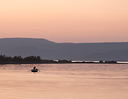 Rowing fisherman on rowboat in harbor at dawn, Skala Kallonis, Lesbos, Greece