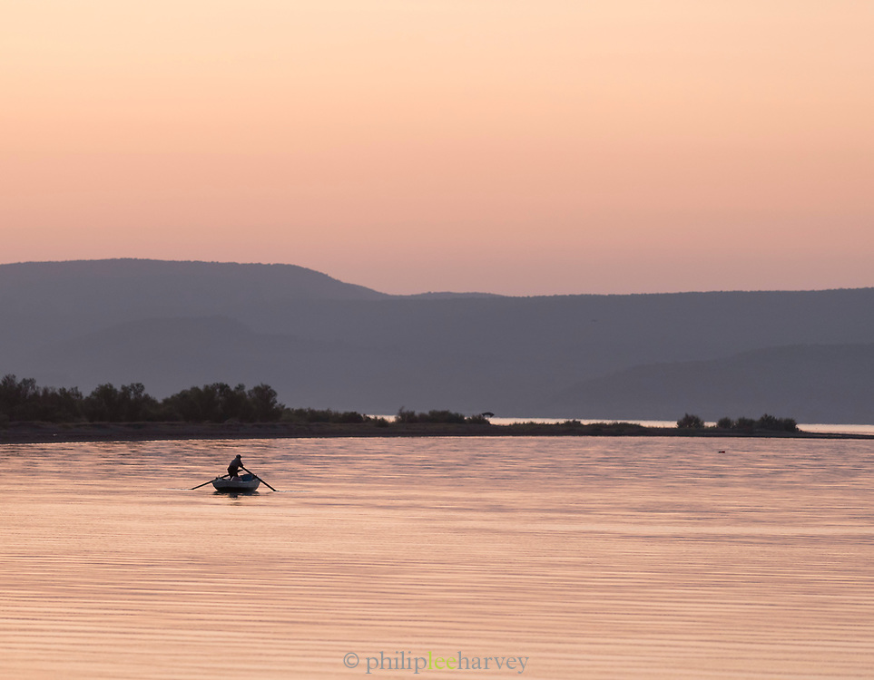 Rowing fisherman on rowboat in harbor at dawn, Skala Kallonis, Lesbos, Greece