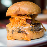 """The """"Manly Burger"""" comprised of beer-cheddar cheese, bacon lardons, smoked-salt onion strings, house ketchup, mustard spread"""