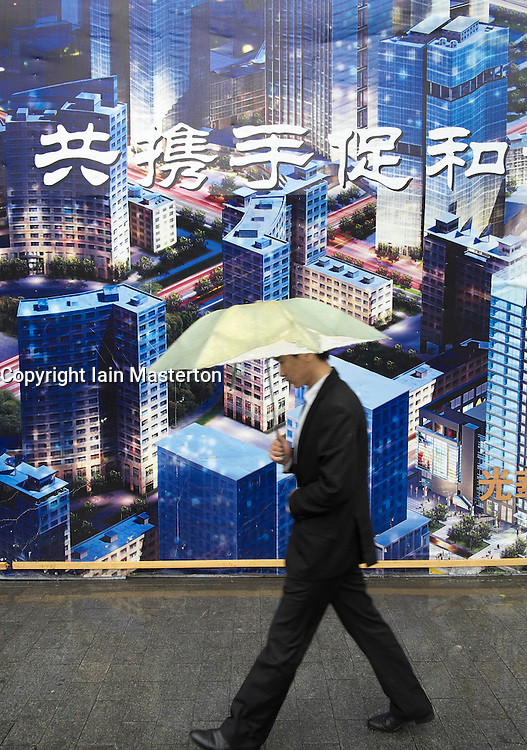 Man walks past billboard showing planned future layout of Central Business District CBD in Beijing China