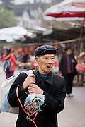 Elderly Chinese man carrying sack through Chongqing, China
