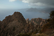 Mountain landscape of the Calanques de Piana, gold and pink coloured granite rock formations formed by wind and rain erosion creating dramatic cavities as they descend into the sea at the gulf of Porto, on 11th September 2017 in Piana, Corsica, France. Corsica is an island in the Mediterranean and one of the 18 regions of France. It is located southeast of the French mainland and west of the Italian Peninsula.