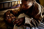 Teresa, 13, helps her aunt, Joanna, 27, to eat some food at the Vilcanculo´s Hospital which is assisted by CARE, Vilanculos, Inhambane province, Mozambique. August 2009. Teresa, took long time before realizing that she has AIDS, she came to the hospital when she couldn´t walk and talk. She is slowly recovering since she started taking antiretroviral drugs. For most Africans living with HIV, antiretroviral drugs are still not available. Unitaid, a program financed by a new mechanism that charges a small fee to airline tickets, has raised $1.2 billion over the past three years for treatments of HIV, malaria and tuberculosis in poor countries.