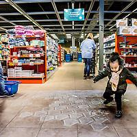 Nederland, Purmerend , 17 januari 2017. Albert Heijn XL in Purmerend.<br />In de allernieuwste XL van Nederland wordenklanten volop geïnspireerd door nieuw assortiment en innovatieve concepten. Vers speelt een hoofdrol in de nieuwe Albert Heijn XL. Klanten zien door de hele winkel vernieuwende versconcepten zoalsverse vis op ijs en een sappen- en yoghurtbar. De winkeltrip wordt een beleving met de 'chooseityourself'-concepten zoalskruiden plukken inde kruidentuin, schaal- en schelpdieren scheppen of je favorietehagelslagsamenstellen.En door een fors aantal energiebesparende maatregelen mag de XL in Purmerend zich de duurzaamste supermarkt van Europa noemen.<br />Op de foto: Kind speelt met interactieve projectie vloerspelletje<br />Foto: Jean-Pierre Jans