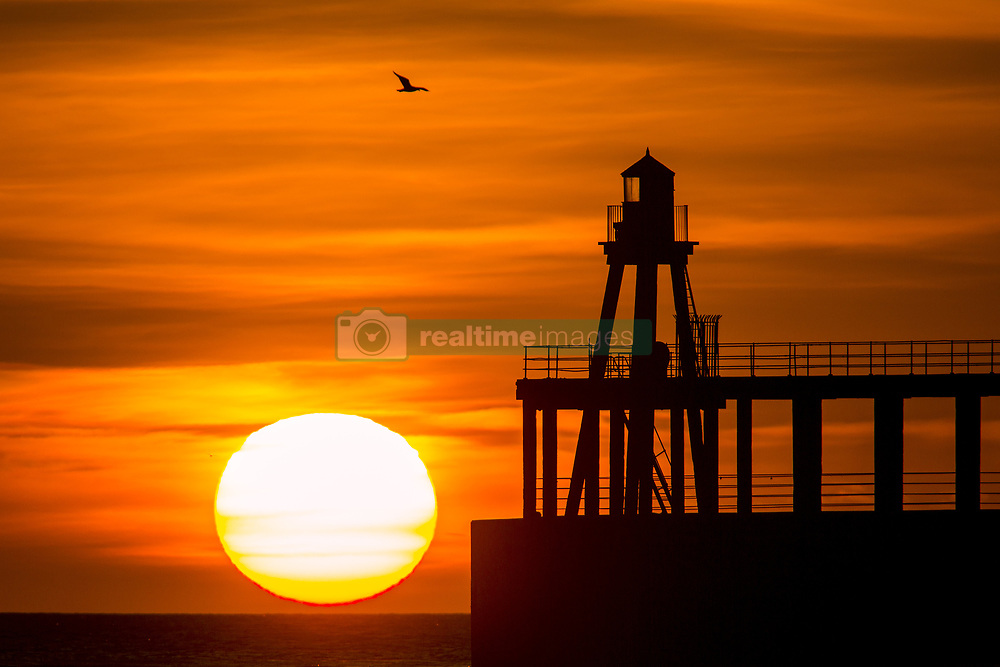 April 26, 2018 - Whitby, Yorkshire, UK - The sun rising this morning behind the lighthouse at the end of Whitby pier on the Yorkshire coast. (Credit Image: © Andrew Mccaren/London News Pictures via ZUMA Wire)