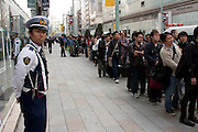 Police Officers control the lines of people at the Apple store awaiting the official release of the iphone4S in Ginza, Tokyo, Japan. Friday October 14th 2011. The latest version of the popular iphone was released worldwide on October 14th. Japans flagship Apple store in Ginza was opened at 8am for the 800 people that had been waiting to be the first to purchase the new telephone.