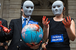 Extinction Rebellion activists dressed as faceless financiers with their hands covered in fake blood taken from a globe assemble in front of the Mansion House for a Blood Money March through the City of London on 27th August 2021 in London, United Kingdom. Extinction Rebellion were intending to highlight financial institutions funding fossil fuel projects, especially in the Global South, as well as law firms and institutions which facilitate them, whilst calling on the UK government to cease all new fossil fuel investment with immediate effect.