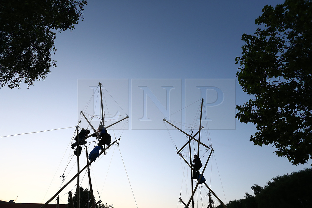 © Licensed to London News Pictures. 15/07/2021. Scunthorpe, UK.  Animal Rebellion activists sit atop bamboo structures outside OSI Food Solutions in Scunthorpe, where they have set up a blockade. The food manufacturing company supply McDonald's restaurants, which Animal Rebellion accuse of mass exploitation of animals and environmental irresponsibility. Photo credit: Adam Vaughan/LNP