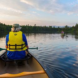 A man and two women canoe on Long Pond near the Appalachian Mountain Club's Gorman Chairback Lodge. Maine's 100 Mile Wilderness.