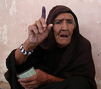An old woman in the Helmand capital Lashkar Gah clutches her voting card and shows off her ink-stained finger, indicating she's voted in the Afghanistan presidential elections.