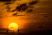People on the beach silhouetted by the rising sun on a cloudy morning June 5, 2017 in Folly Beach, South Carolina. Folly Beach is a quirky beach community outside Charleston known to locals as the Edge of America.