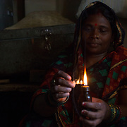 CAPTION: Sulochana Devi lights a small flame powered by kerosene, the way the villagers of Singhilpur have lit up their dark homes since as long as they can remember. LOCATION: Singhilpur, Saran District, Bihar, India. INDIVIDUAL(S) PHOTOGRAPHED: Sulochana Devi.