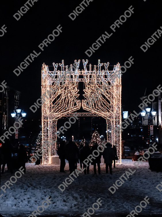 Montreal, Quebec, Canada - January 3, 2021 Traditionally winter and christmas lights placed in Jacques Cartier square in Old Port on Montreal surrounded by unrecognizable people and snow at night