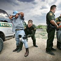 Verenigde Staten.Arizona.Nogales.juli 2005.<br /> Grenspolitie arresteert illegale vluchtelingen in de woestijn van Zuid Arizona, die illegaal vanuit Mexico de Verenigde Staten zijn binnengekomen. Ze worden gefoullerd op wapens en hun papieren worden gecontroleerd. Daarna worden de illegalen naar het hoofdbureau van de grenspolitie getransporteerd, waarna ze geregistreerd worden alvorens ze terug de grens overgebracht worden.Body check.Controle.Border Patrol.Mexicaan.Grens.Grens problematiek.<br /> Op de foto uiterst rechts Jose Luis Maheda, officier bij de grenspolitie van Nogales.<br /> Archives 2005. Chase by police on illegal Mexicans who cross the border in Arizona.