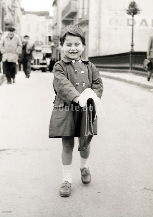 little happy smiling girl with school briefcase posing France ca 1950s