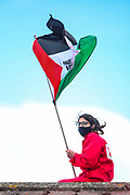 Tamworth, United Kingdom, May 25, 2021:  Palestine action activists stand on the rooftop as they occupied an Israeli owned weapons manufacturer building in Tamworth, Amington Industrial Estate near Birmingham on Tuesday, May 25, 2021. Activists wave Palestinian flag ahead of arrest from the police. (Photo by Vudi Xhymshiti)